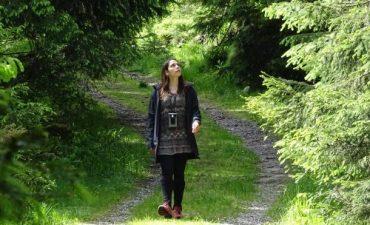 Eine Frau geht durch einen Wald